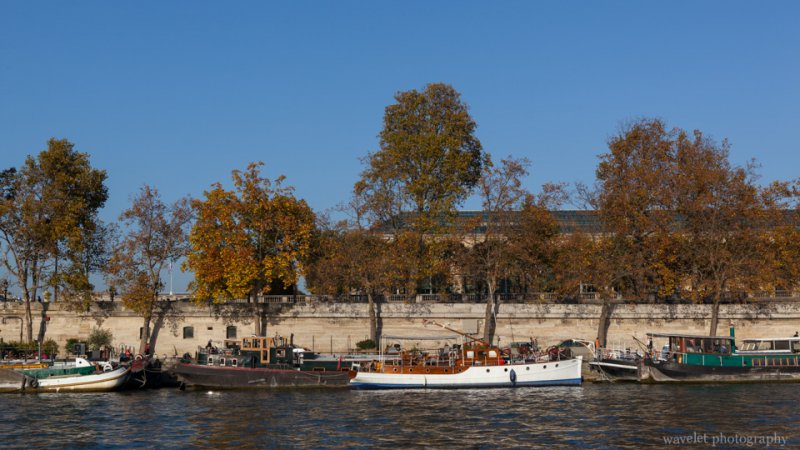 Tourist boats on the Seine River against Musée de l'Orangerie on the Right Bank, Paris