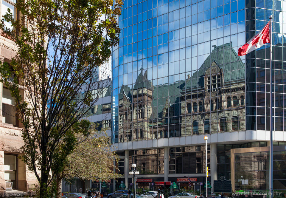 The Old City Hall reflected on the glass exterior of Eaton Centre, Toronto