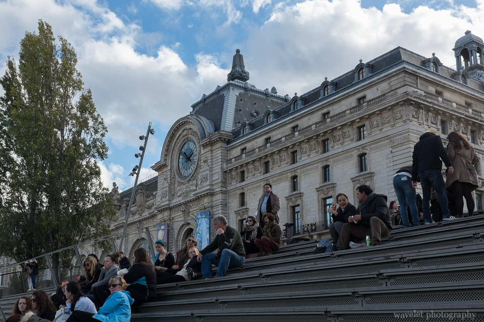 People sitting on the stairs by the River Seine outside of Musée d'Orsay, Paris
