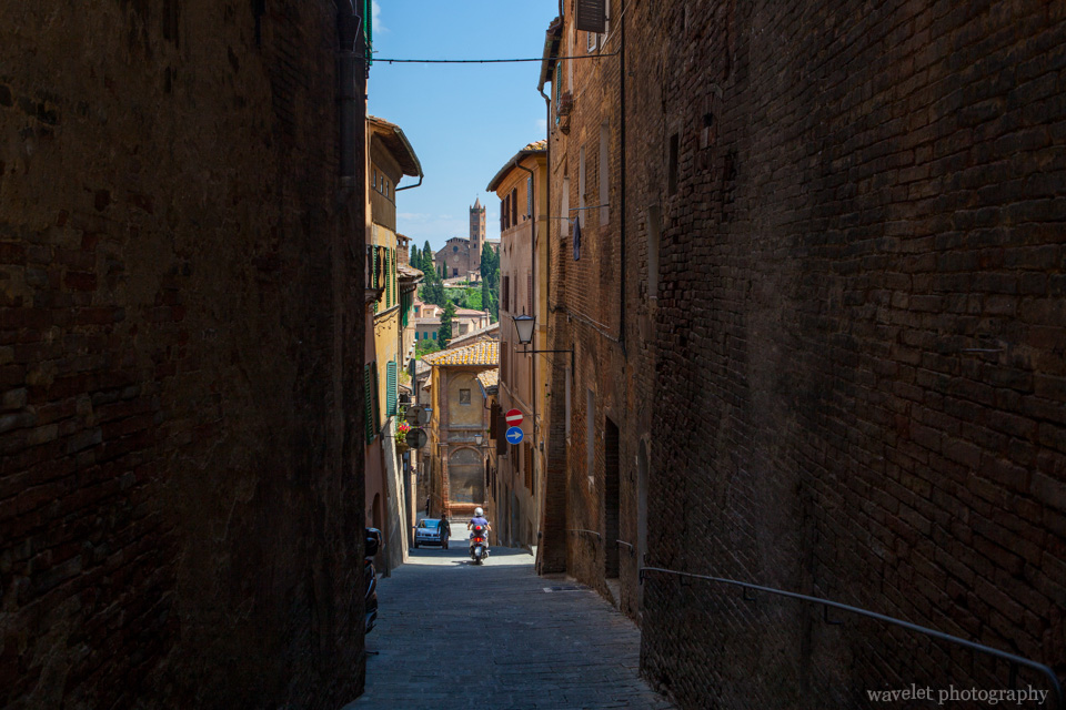 Overlook the church of Santa Maria dei Servi through the narrow street, Siena